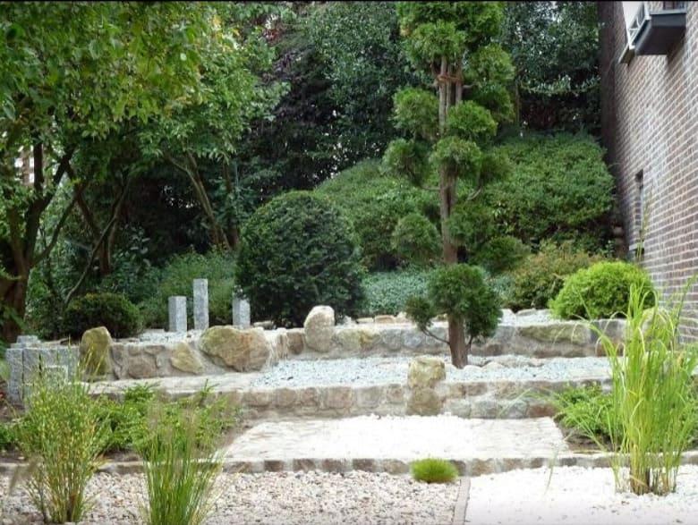 Hanggarten mit Designerpalisaden. Terrasenbau aus Natursteinmauern und kleinen Felsen.
