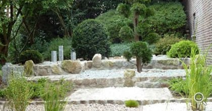 Slope garden with designer palisades. Terraced construction of natural stone walls and small rocks.