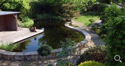 Wooden terrace over swimming pond with brick sandstone cladding.