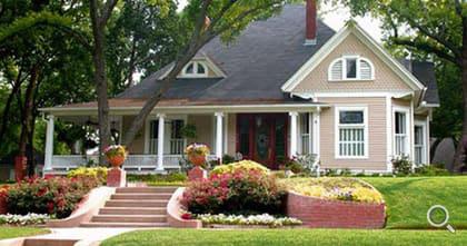 Landhaus mit Treppenwange im bepflanzten Vorgarten.
