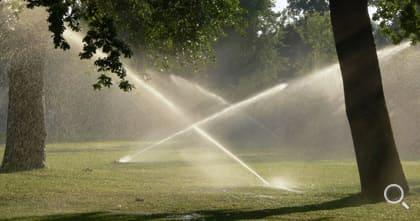 Automatisches Bewässerungssystem. Rasenbewässerungsanlage für eine größere Grünanlage.