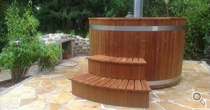 Hot tub (wooden bathtub) with fireplace wood storage on paved floor.