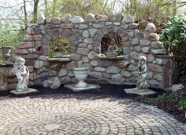 Garden place paved and natural stone wall with statues and Buddha.