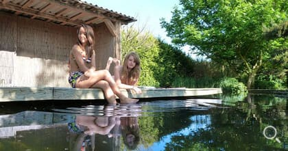 Two girls enjoy the relaxation at the garden pond.