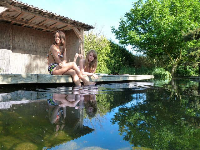 Zwei Mädchen genießen die Erholung am Gartenteich.